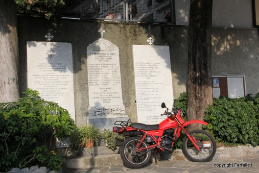 Red motorcycle in front of tablets commemorating war dead.
